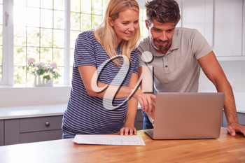 Couple With Pregnant Wife At Home Buying Products Or Services Online Using Laptop