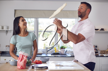 Man Flipping Base As Couple In Kitchen Home Prepare Homemade Pizzas Together