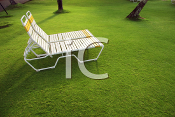Royalty Free Photo of Resort Lounge Chairs on Lush Green Grass