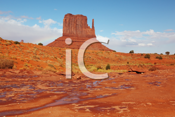 The majestic Monument Valley. Puddles after the rain among 'Mittens'