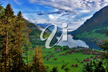Lake, meadows and a village in Switzerland mountains