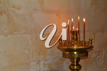Bronze Floor candlestick with burning candles. Background - a stone wall