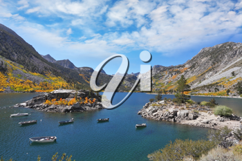 Fisherman's Paradise. Azure lake in the autumn mountains. Fishing boats circling around a small picturesque island