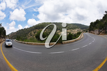 The car on abrupt turn of the mountain road, photographed by an objective  Fish eye
