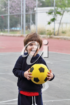 A lovely little boy played happily with a yellow ball on the playground