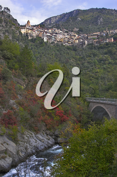 Picturesque settlement in mountains and the stone bridge through a rough mountain stream