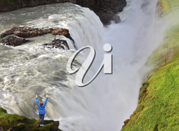 The delighted woman - tourist over  water chasm. Enormous falls Gyullfoss. Summer in Iceland