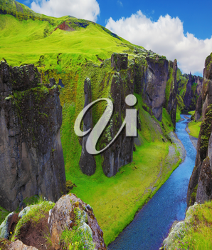 Fantastic country Iceland. The most picturesque canyon Fjadrargljufur  and the shallow creek, which flows along the bottom of the canyon