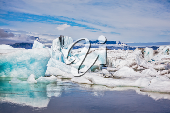 Floating ice and clouds reflected in the mirror-smooth water lagoon Ice Jokulsarlon. Ice splendor. Iceland