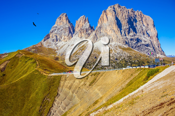 Indian summer in the Tyrol. Magnificent ridge of dolomite rocks on the Sella Pass, Dolomites. Picturesque road through the pass. The concept of extreme and ecological tourism