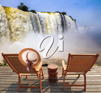 Incredible exotic waterfalls of Iguazu in South America. Two comfortable wooden chaise lounges face waterfalls. On one hangs an straw female hat. Concept of active and eco-tourism