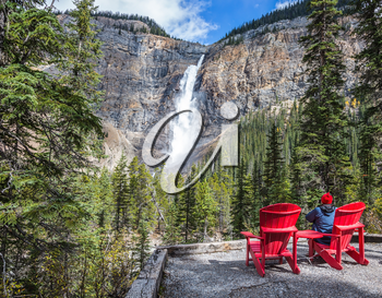 Elderly woman photographs the famous waterfall. Two red deck chairs to relax in front of the waterfall Takakkaw. Autumn day in Yoho National Park in the Rocky Mountains