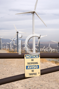 Royalty Free Photo of a Wind Turbine Farm With a Notice of No Trespassing
