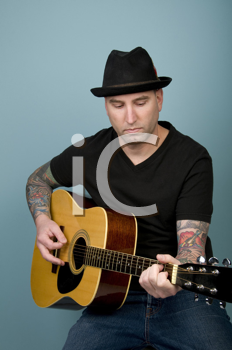Royalty Free Photo of a Tattooed Guy Playing Guitar