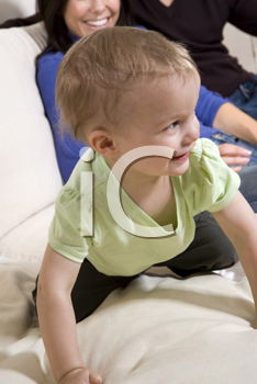 Baby boy crawling on the sofa with his parents in the background