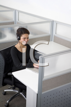 Royalty Free Photo of a Black Woman Wearing a Headset in a Cubicle
