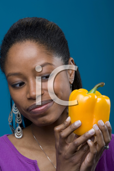 Royalty Free Photo of a Black Woman Looking at a Yellow Pepper