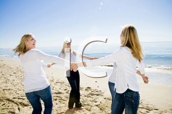 Royalty Free Photo of Four Women on the Beach Holding Hands