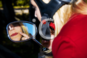 Royalty Free Photo of a Woman on a Scooter Checking Her Lipstick