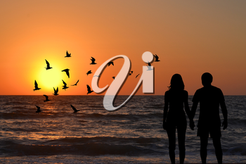 View of a full body of couple silhouettes holding hands looking at sunrise on the beach