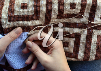 Woman embroidering traditional pattern with geometric design