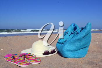 Summer concept with bag, hat, sun glasses and flip flops on beach