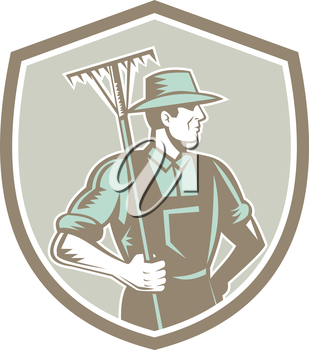 Illustration of organic farmer holding rake on shoulder facing side set inside shield crest on isolated background done in retro woodcut style.