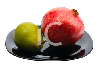 Pomegranate and pear on a black platte, isolated.