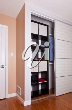 Built-in closet with sliding door shelving storage organization solution filled with clothes