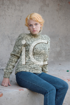 Blonde woman in a green sweater posing outdoors