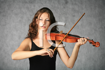 portrait of sexy brunette with violin on the grey background