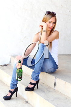 Cute female sitting on the stairs with bottle of vine