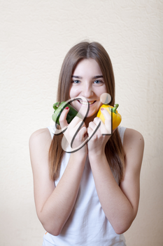 blond girl having fun with colorful peppers on the beige background. Healthy nuitrition foood concept