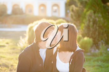 Happy couple against the background of park kissing, backlit composition, togetherness concept, love and tenderness