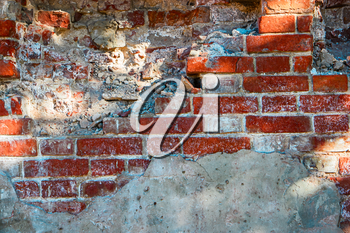 Grungy brick wall half covered with cement