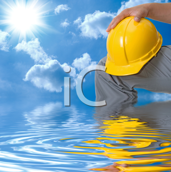 Royalty Free Photo of a Builder Holding a Hardhat in Water
