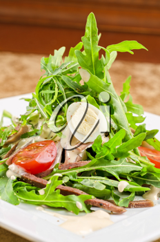 Tasty salad of beef tongue with eggs, arugula, tomato, spices and sauce