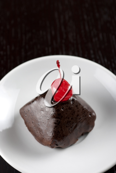 fresh baked chocolate cupcake with cherry on a wooden table