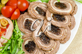 Cutting meat tenderloin with prune with lettuce, tomatoes and Ruccola