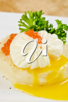poached eggs in a nest of mashed potatoes with greens and caviar