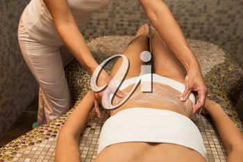 Woman having abdomen massage with cream at spa, closeup photo. Beauty, healthy lifestyle and relaxation concept.