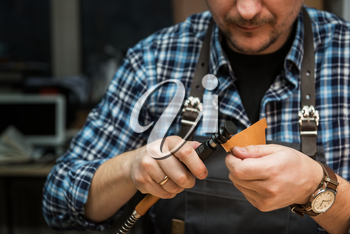 Man working with leather textile at a workshop.