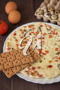 baked omelette with different eggs and vegetables with rye small load of bread