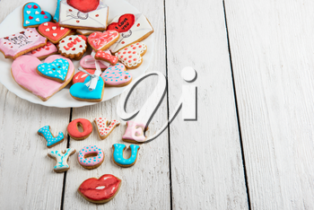Gingerbreads for Valentines Day at plate on white wooden background