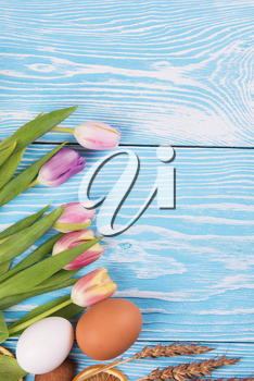 Composition of tulips and gingerbread cookies on white and blue wooden background for Happy Easter.