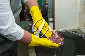 Hands in gloves washing and cleaning meat at the kitchen sink