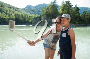 Mother and son taking selfie on mobile phone with stick. Vacation on river in the mountain