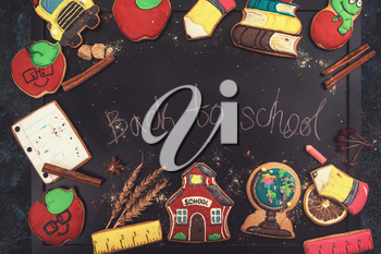 Concept photo of Back to school with gingerbreads cookies on a dark background with school board