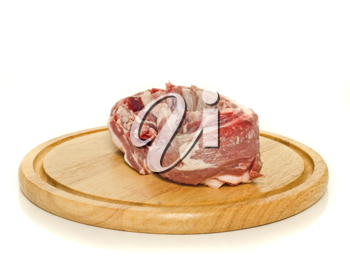 Raw meat on round hardboard over the white background