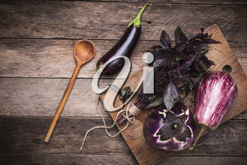Aubergines and basil on and wooden table. Rustic style and autumn food photo
